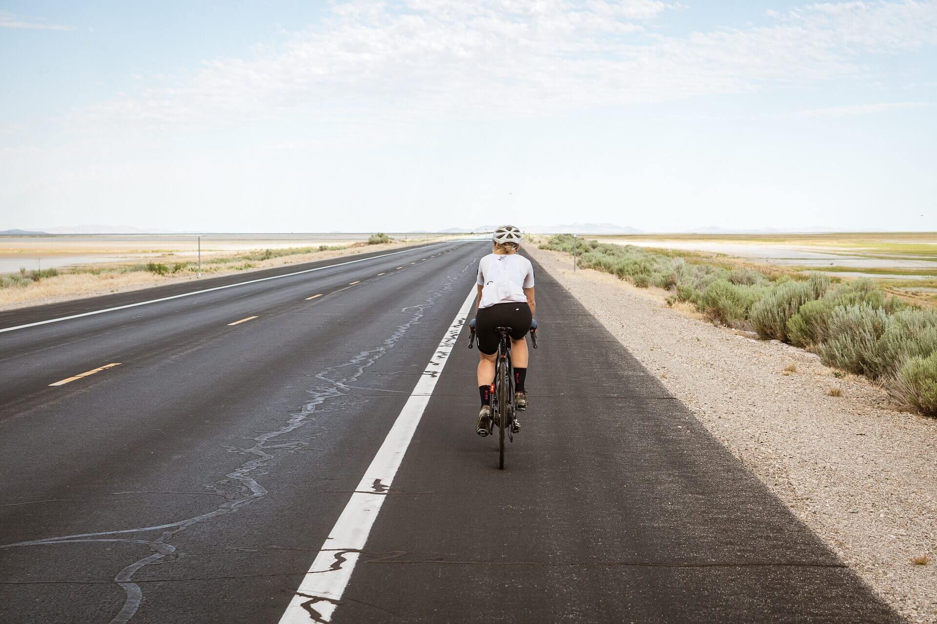 Someone bikes down an em empty road.