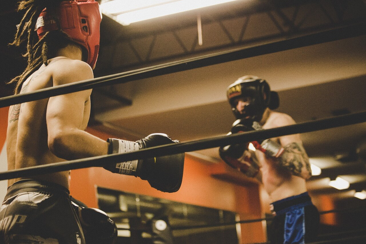 two men in boxing gear spar in a boxing ring.