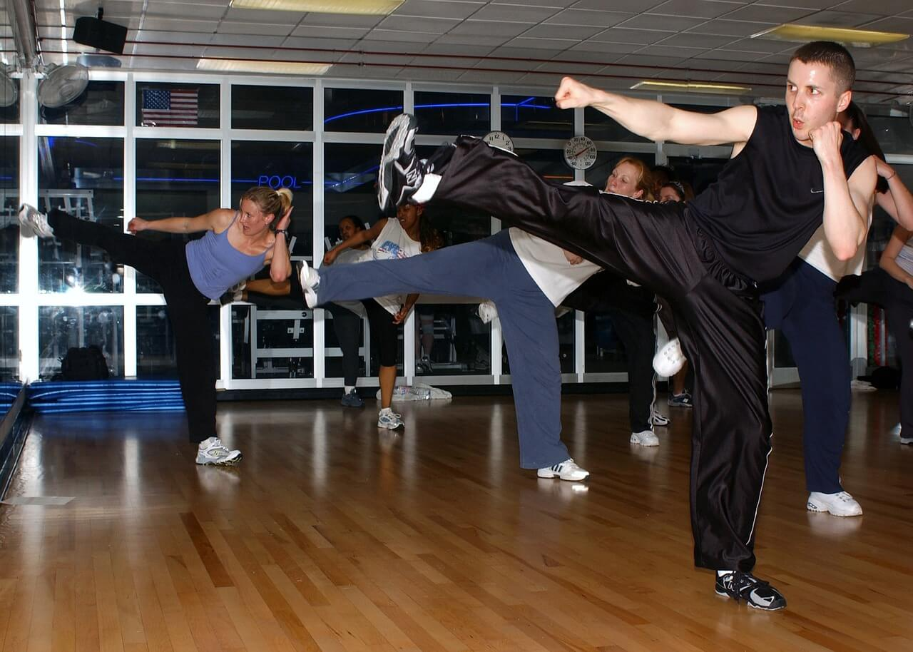 Several people are in a gym participating in a kickboxing class.