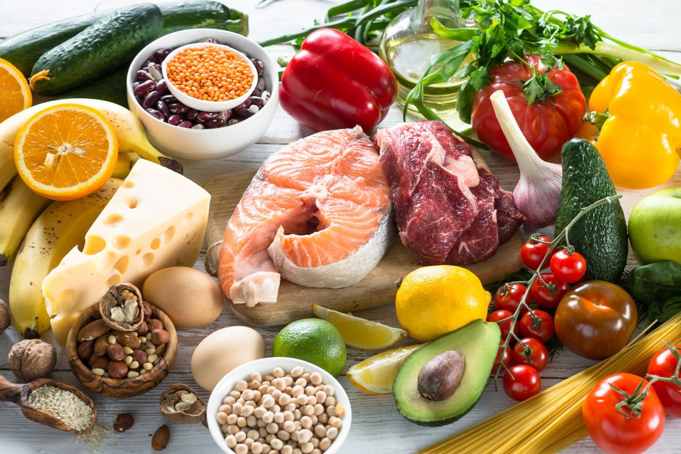 several foods are displayed on a counter. They include meats, cheese, nuts, and fruits.