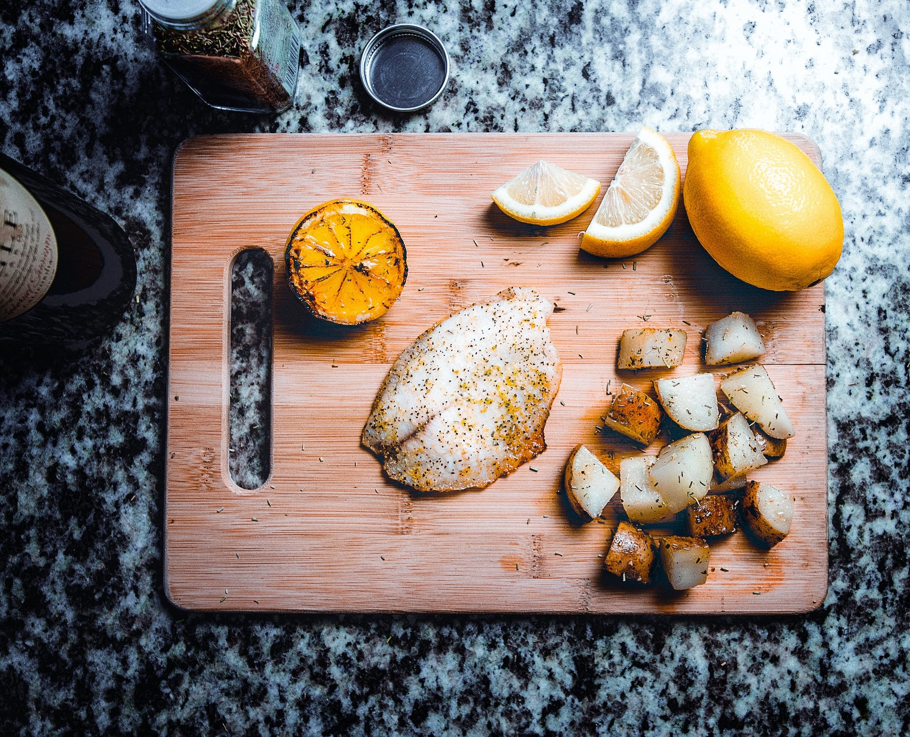 Seasoned fish on a cutting board with lemon and potatoes.
