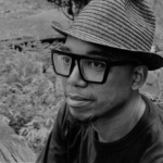 Headshot of Tarish Pipkins in black and white wearing a hat