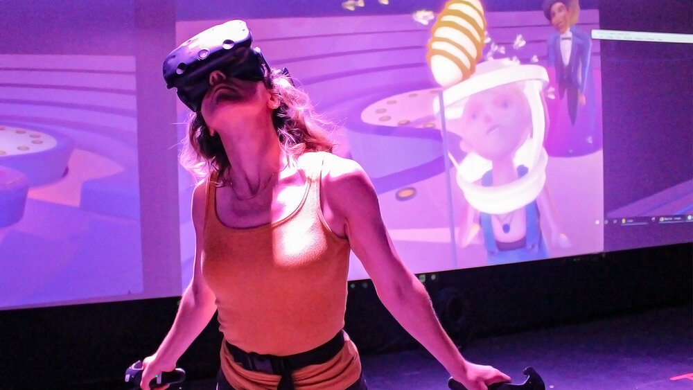 A woman stands with arms behind her with a virtual reality mask over her eyes on her face with a bright purple background