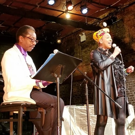 One man sitting on the left reading off a music stand while a woman stands and sings into a microphone