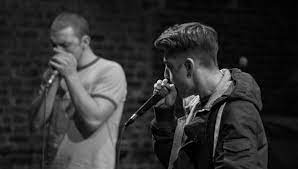 a black and white photo of two performers beat rhyming into microphones