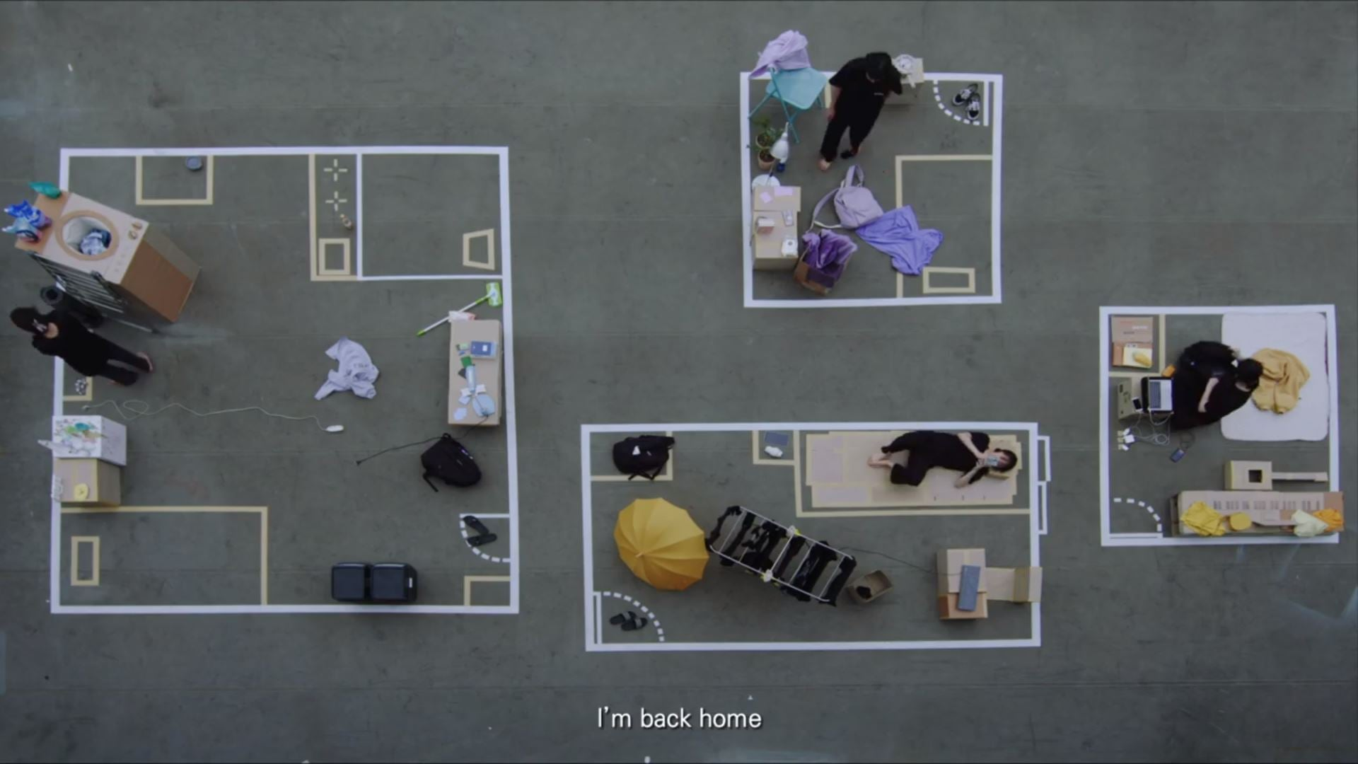 aerial view of performers moving within four different boxes with props outlined in chalk