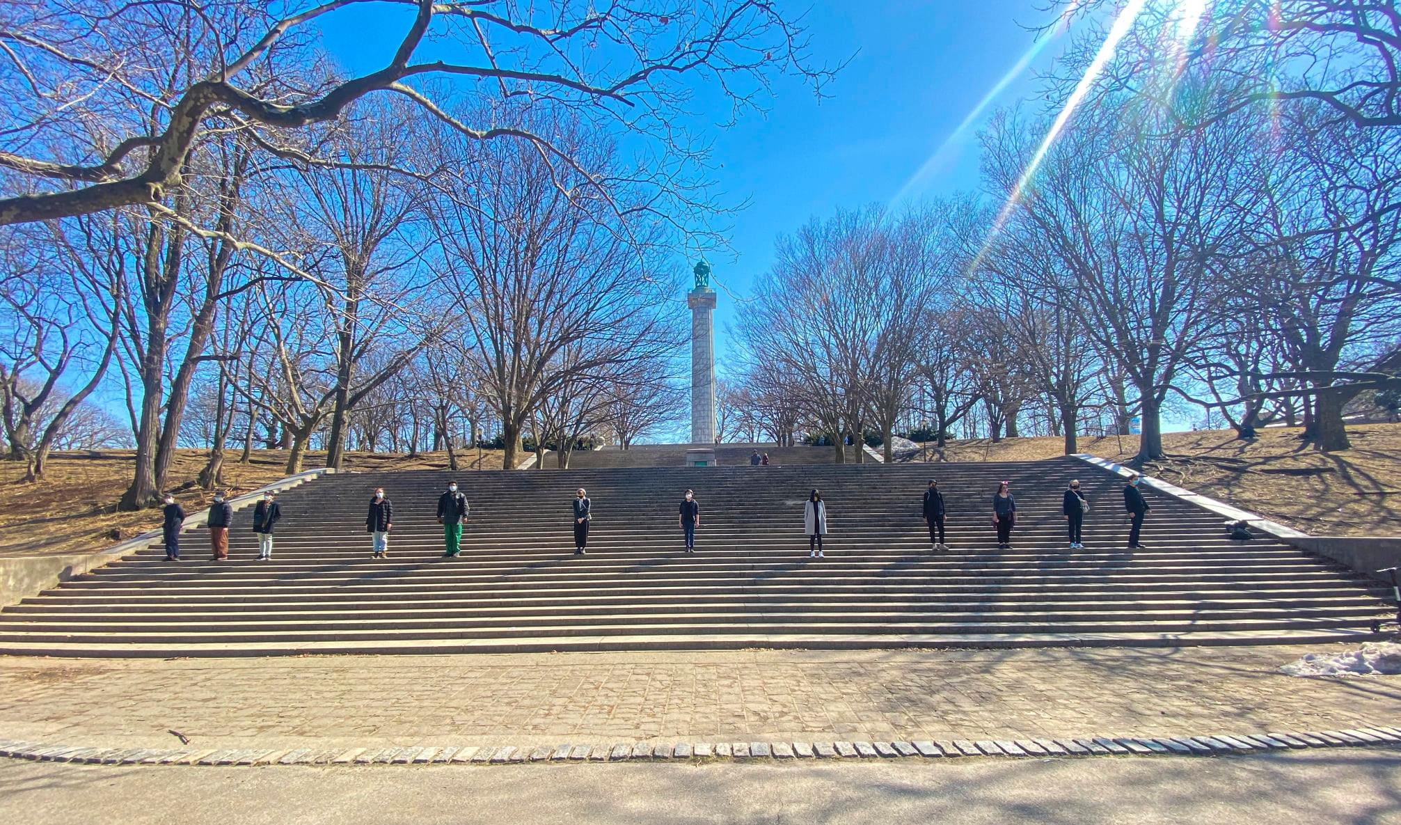 performers stand outside in a park on a large stone staircase with a blue sky and trees