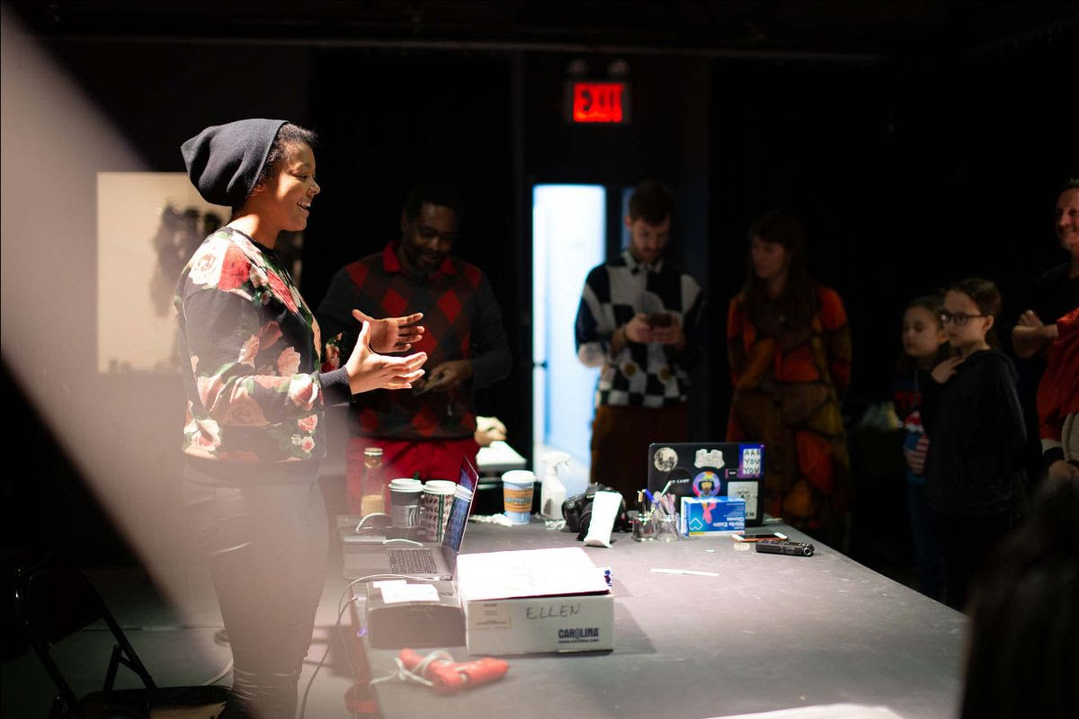 a person stands in front of a table presenting work to an audience