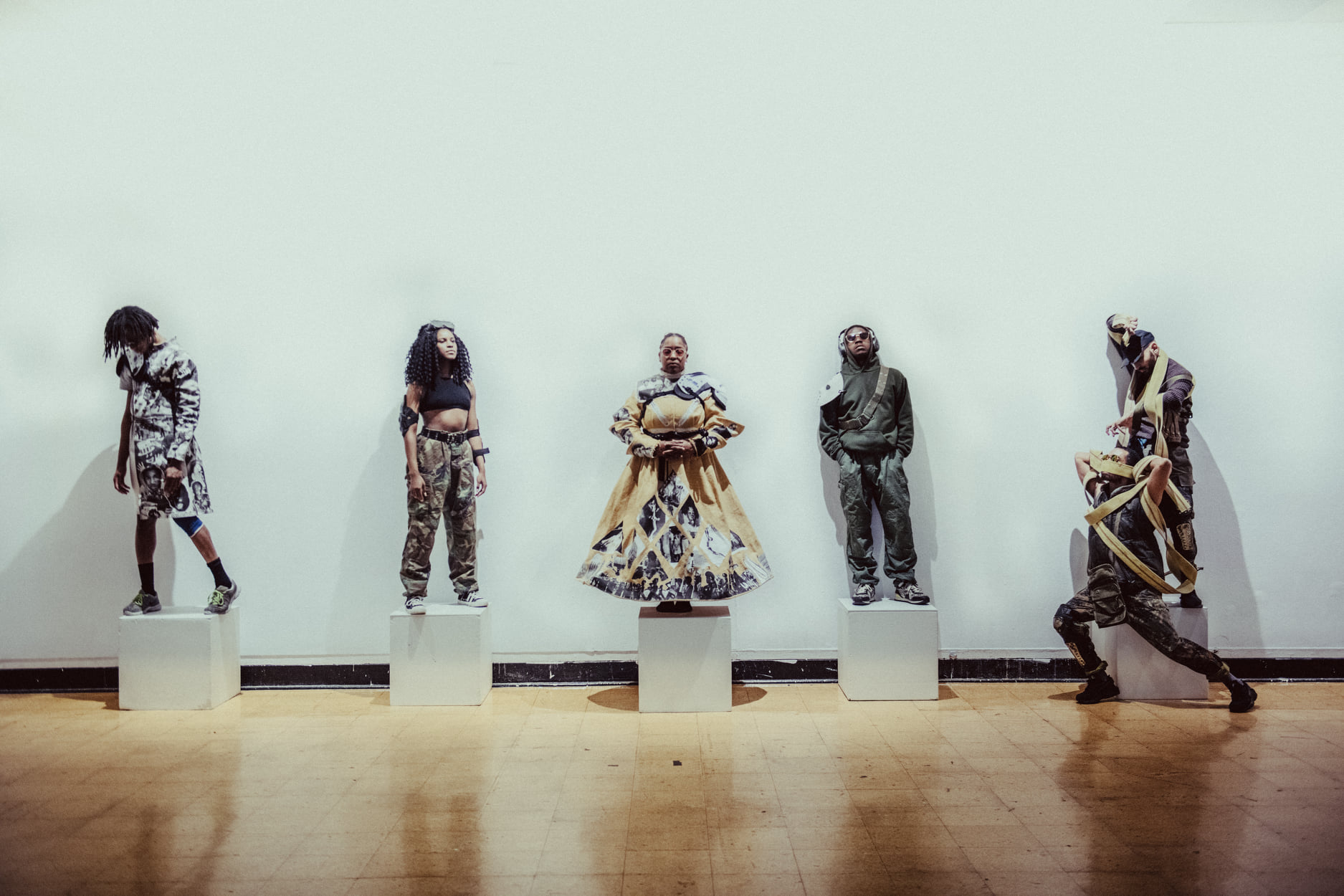 five performers stand in a line across the frame on white cubes with a white background on a wood floor