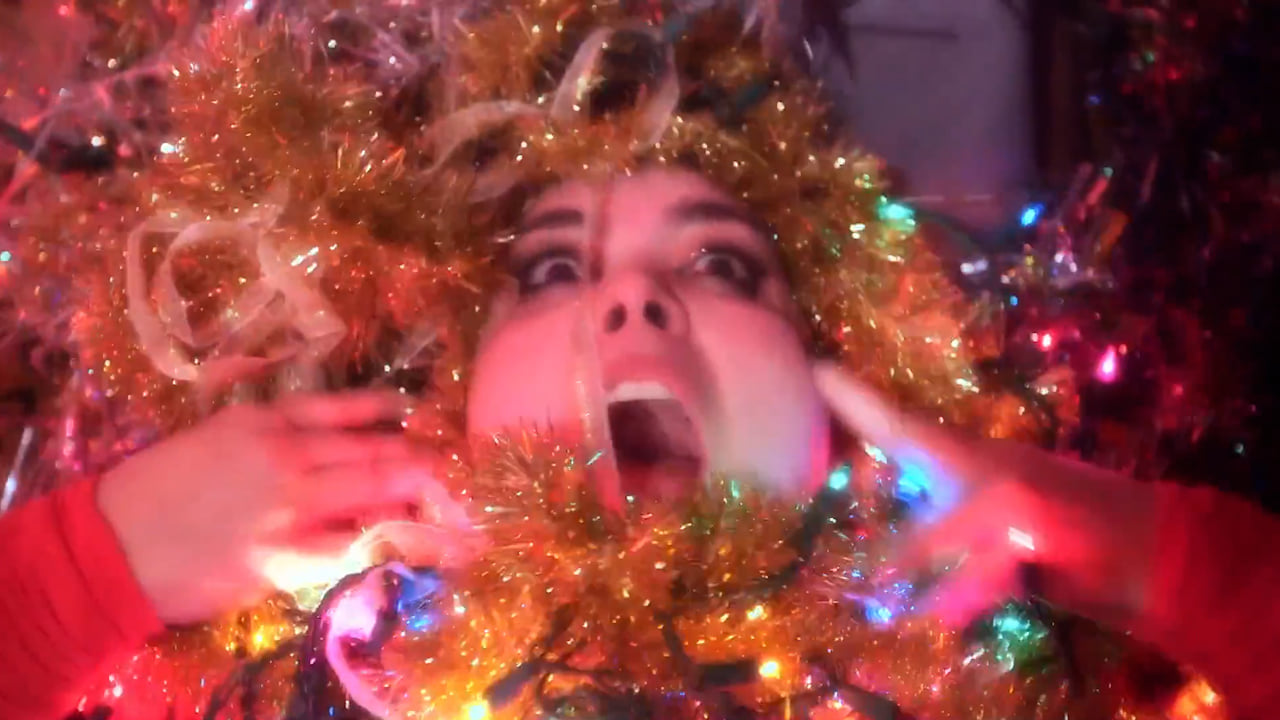 a performer covered in lights and fabrics puts her hands on her cheeks with mouth open in a headshot