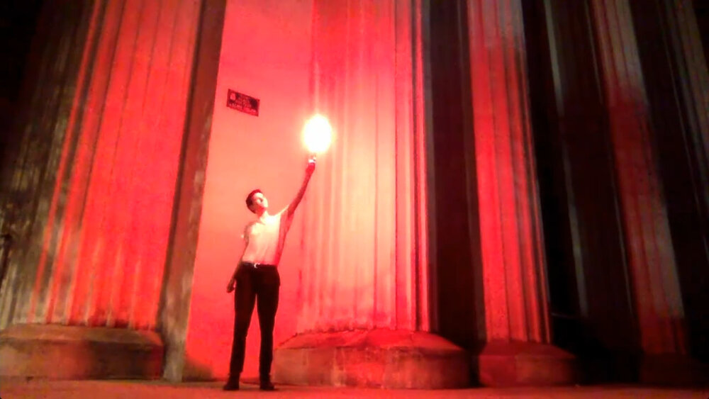 red light on a person dressed in white standing on stairs with white columns behind illuminated holding a bright light