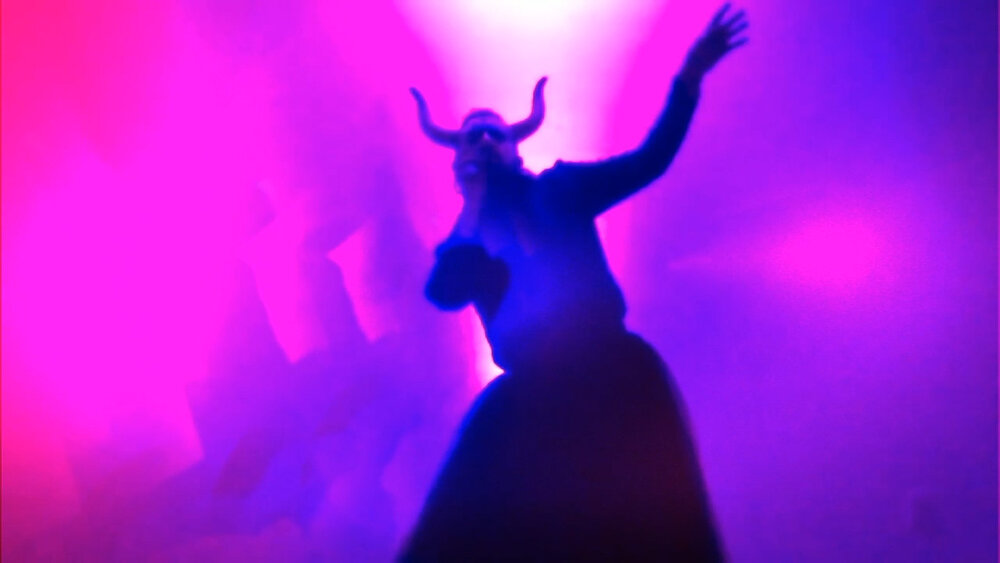 purple and pink image of a demon like figure with hand extended upwards with horns