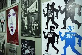 a photo of the la mama archive with old show posters on the wall in many colors