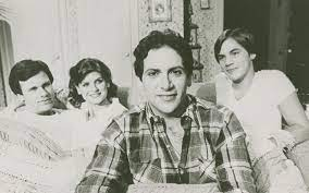 a black and white photo of Harvey Fierstein from the la mama archive with three people sitting behind him looking at him smiling