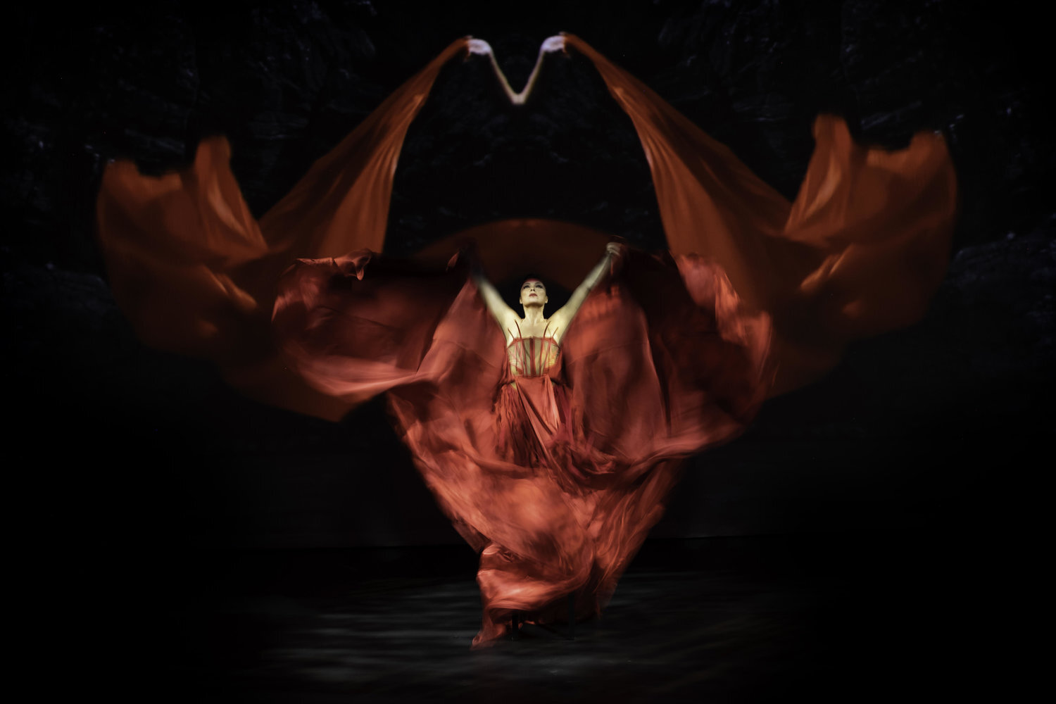 a native american performer extends her hands on a black stage covered in flowing red fabric from floor to ceiling