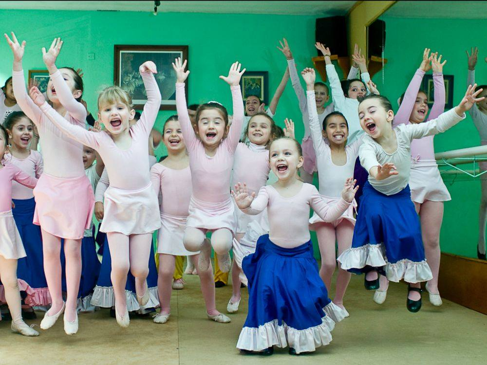 tiny ballerinas cheer and celebrate with arms in the air in front of a green wall
