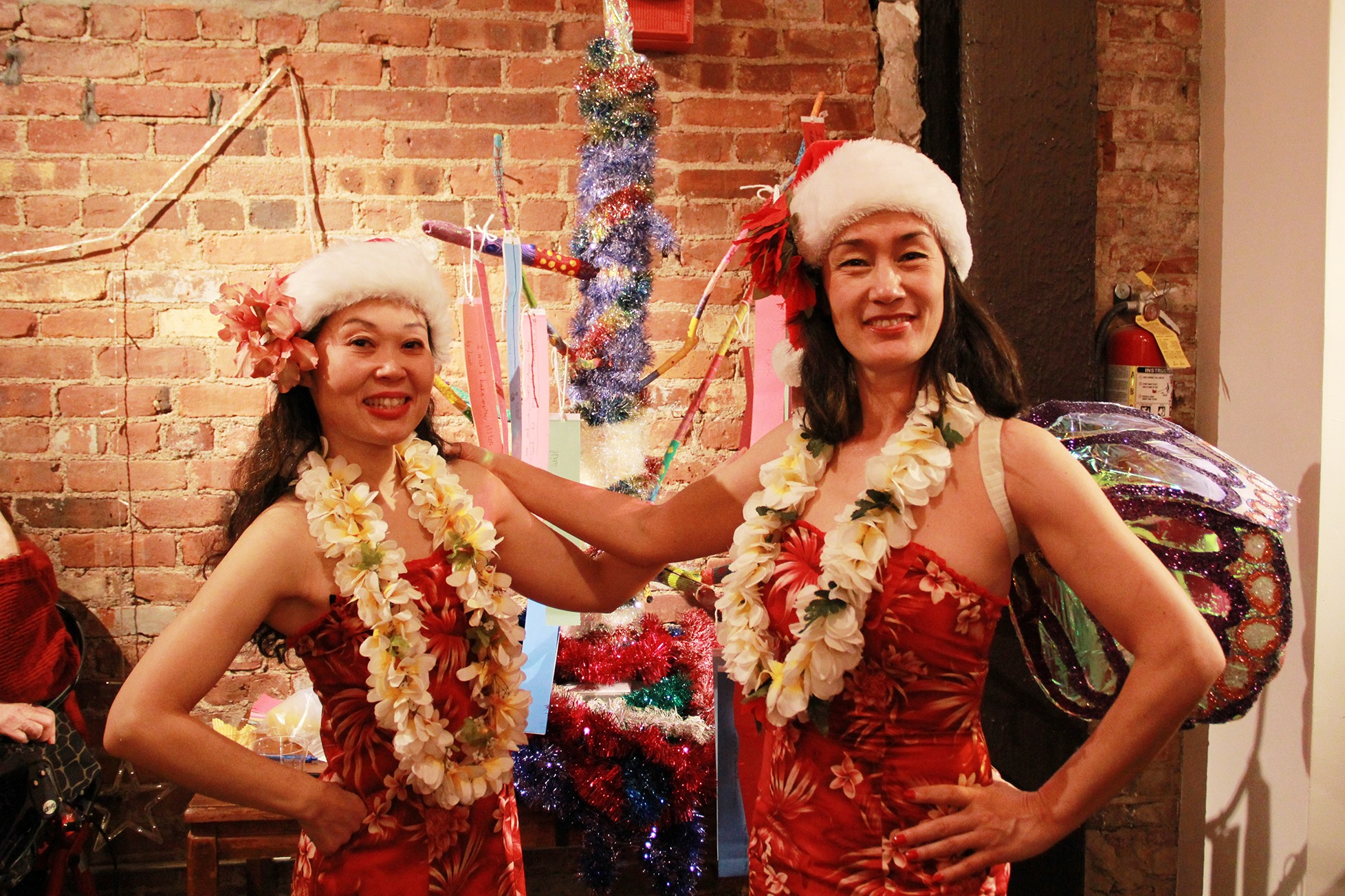 two hula dancers dressed in red embrace in front of a red brick wall they are both wearing santa hats