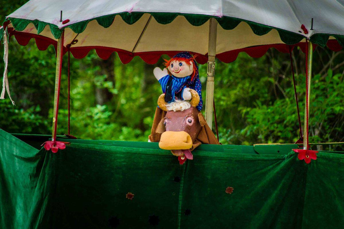 a fun puppet with red hair stands on stage in front of trees