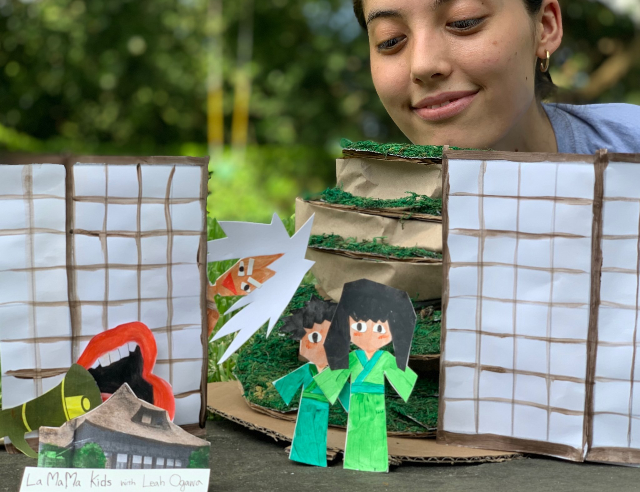 leah ogawa stands in a garden looking at her paper puppets who appear to be paper and dressed in green