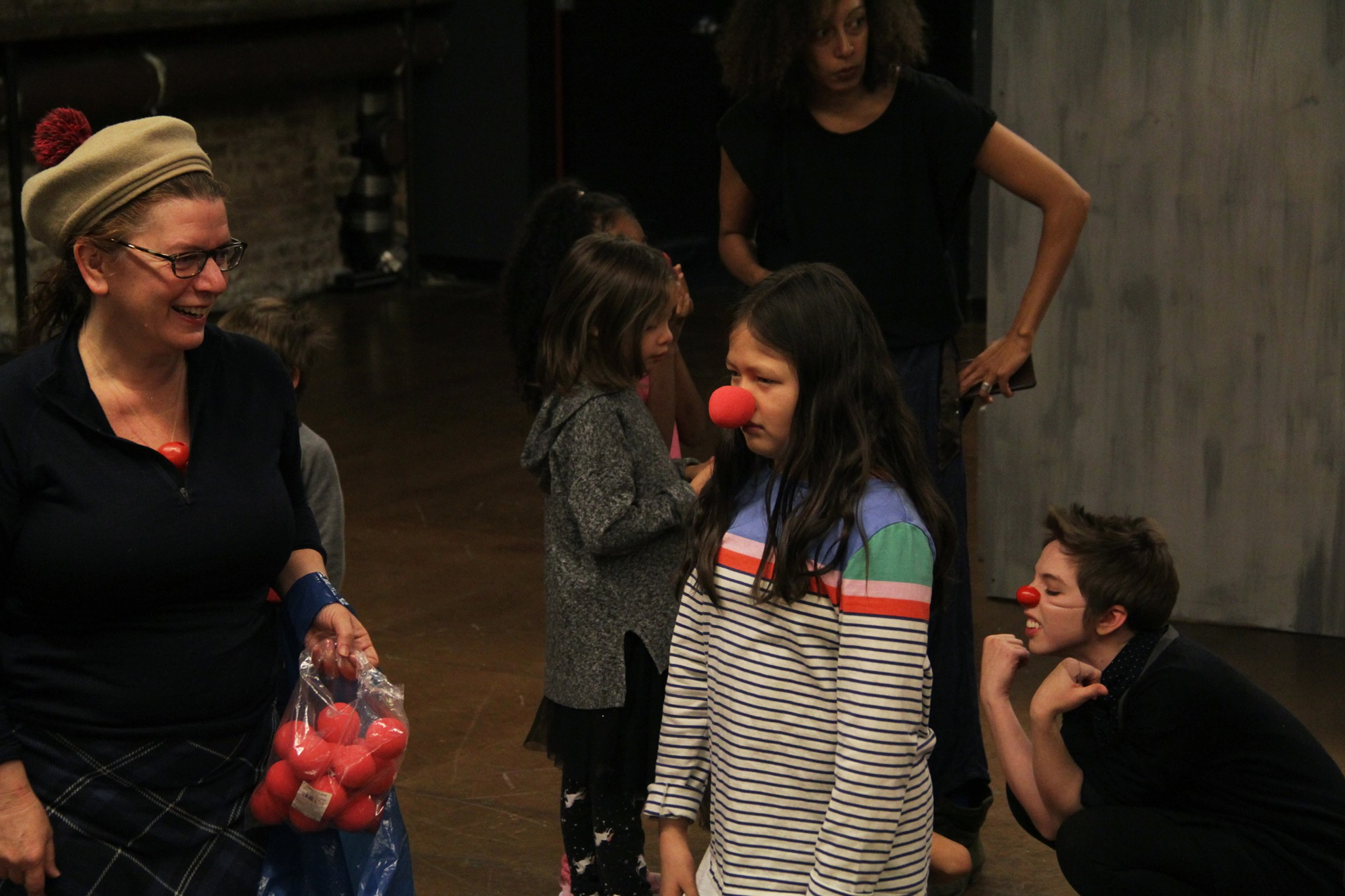 a woman instructs young people in a clowning workshop with one wearing a red nose at la mama
