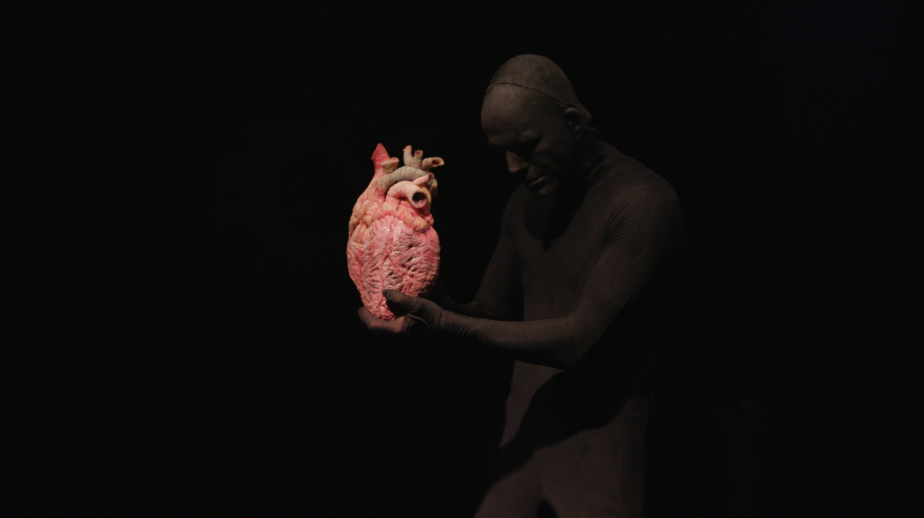 a puppeteer dressed in black holds a realistic heart puppet in his hands