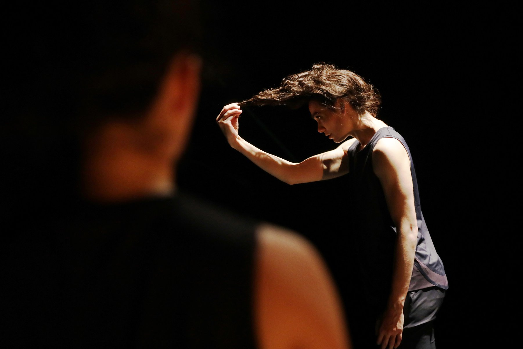 a woman grabs her pony tail strongly as another woman watches on a dark stage