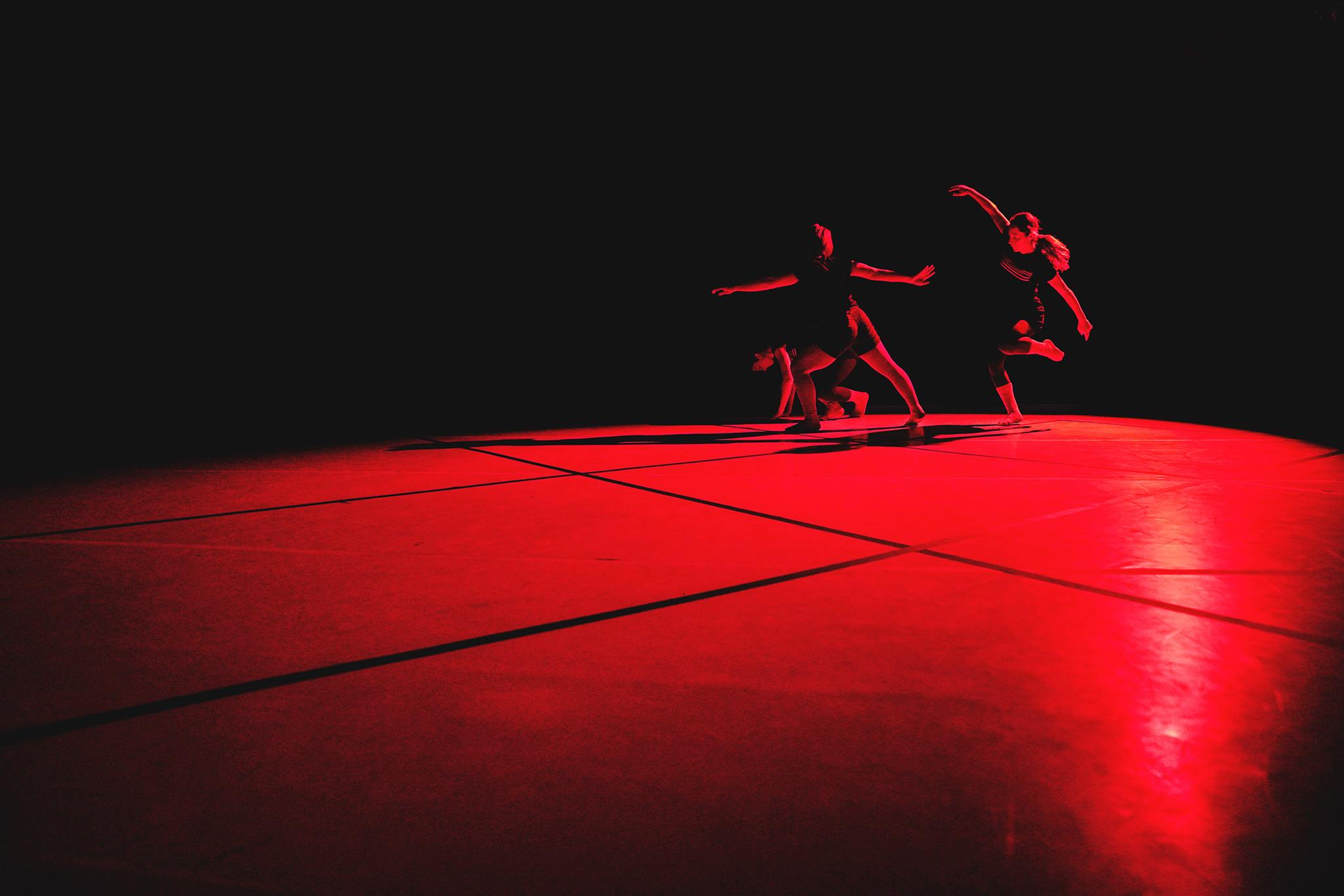 three dancers move on a red lit floor