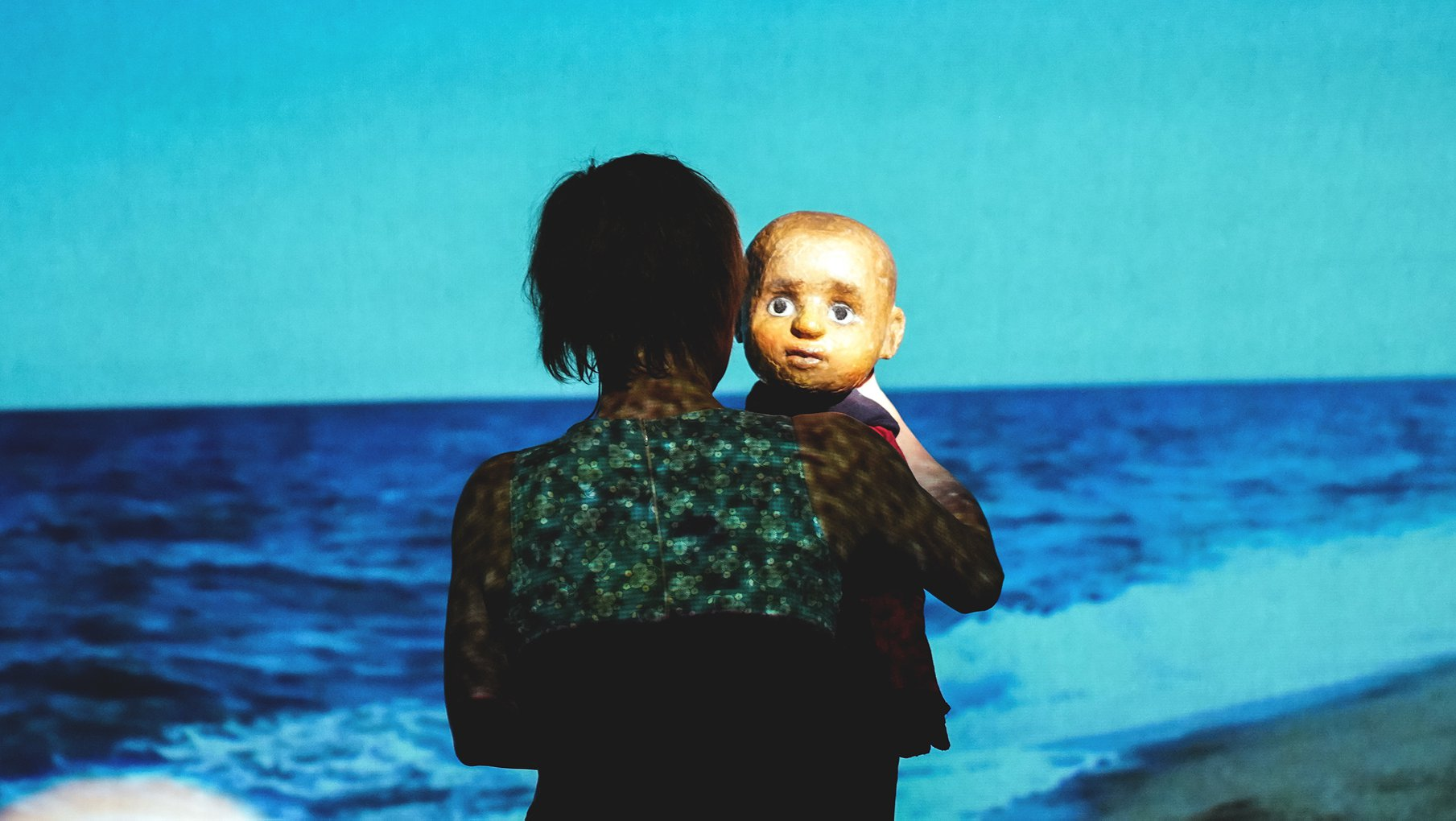 projected image of a beach with a woman with her back to the audience holding a puppet of a little boy looking straight into the camera