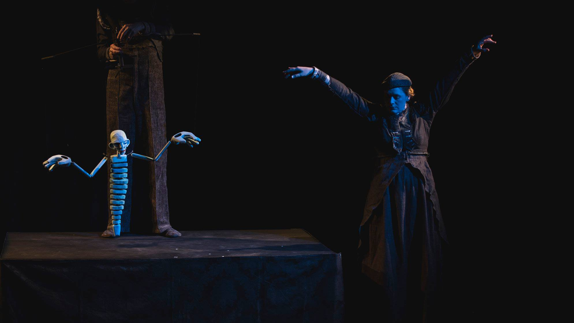 a performer stands next to a puppet on a dark stage they both have their arms in the air