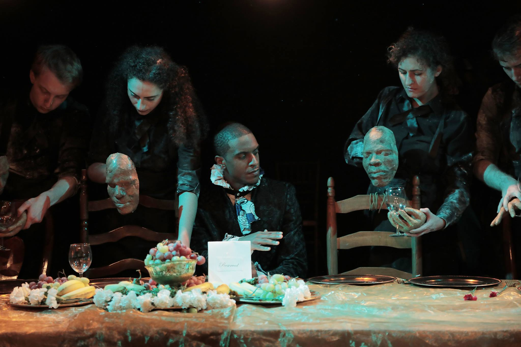 various puppet faces manipulated at a dinner table with a man in the middle sitting and eating next to empty chairs