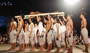 Trojan Women Project performers standing in two lines shirtless in the same grey pants carrying sticks above their heads