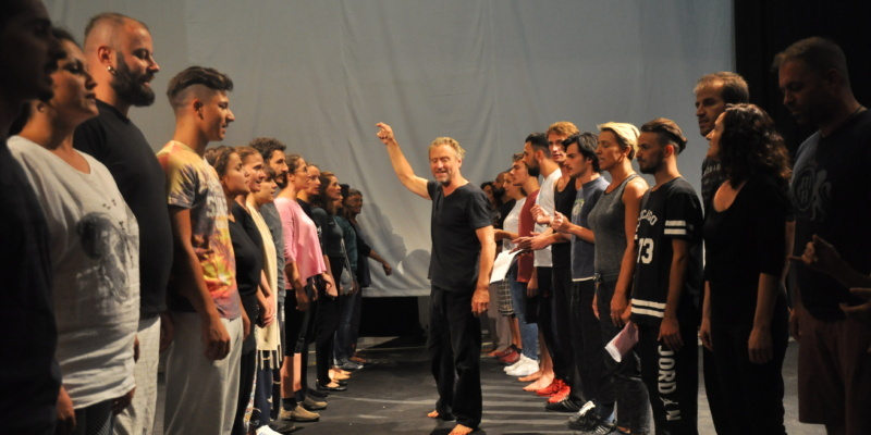 The Trojan Women Project standing in a rehearsal in two lines in Kosovo