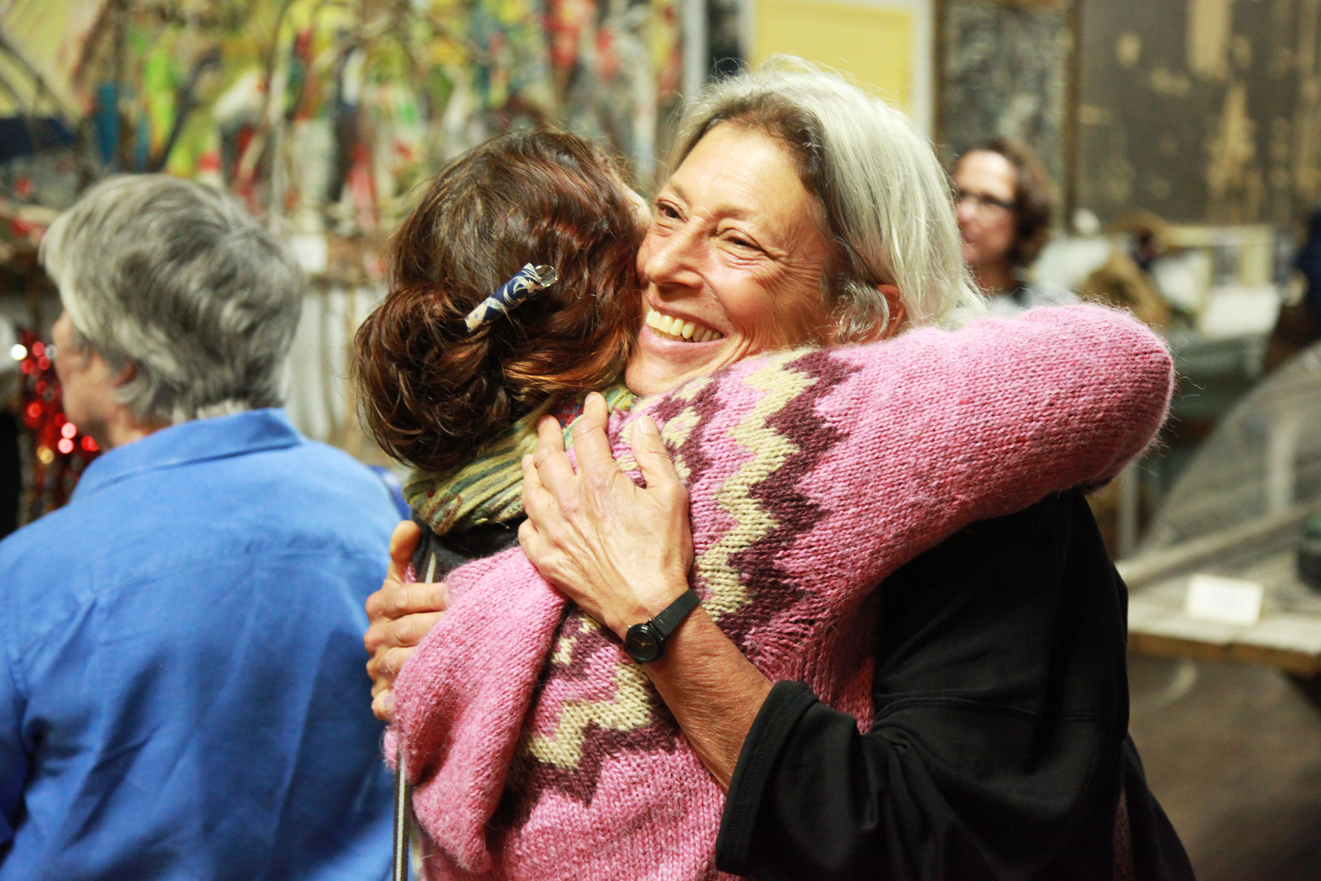 Onni Johnson hugging a woman in a pink sweater at a Trojan Women Project event
