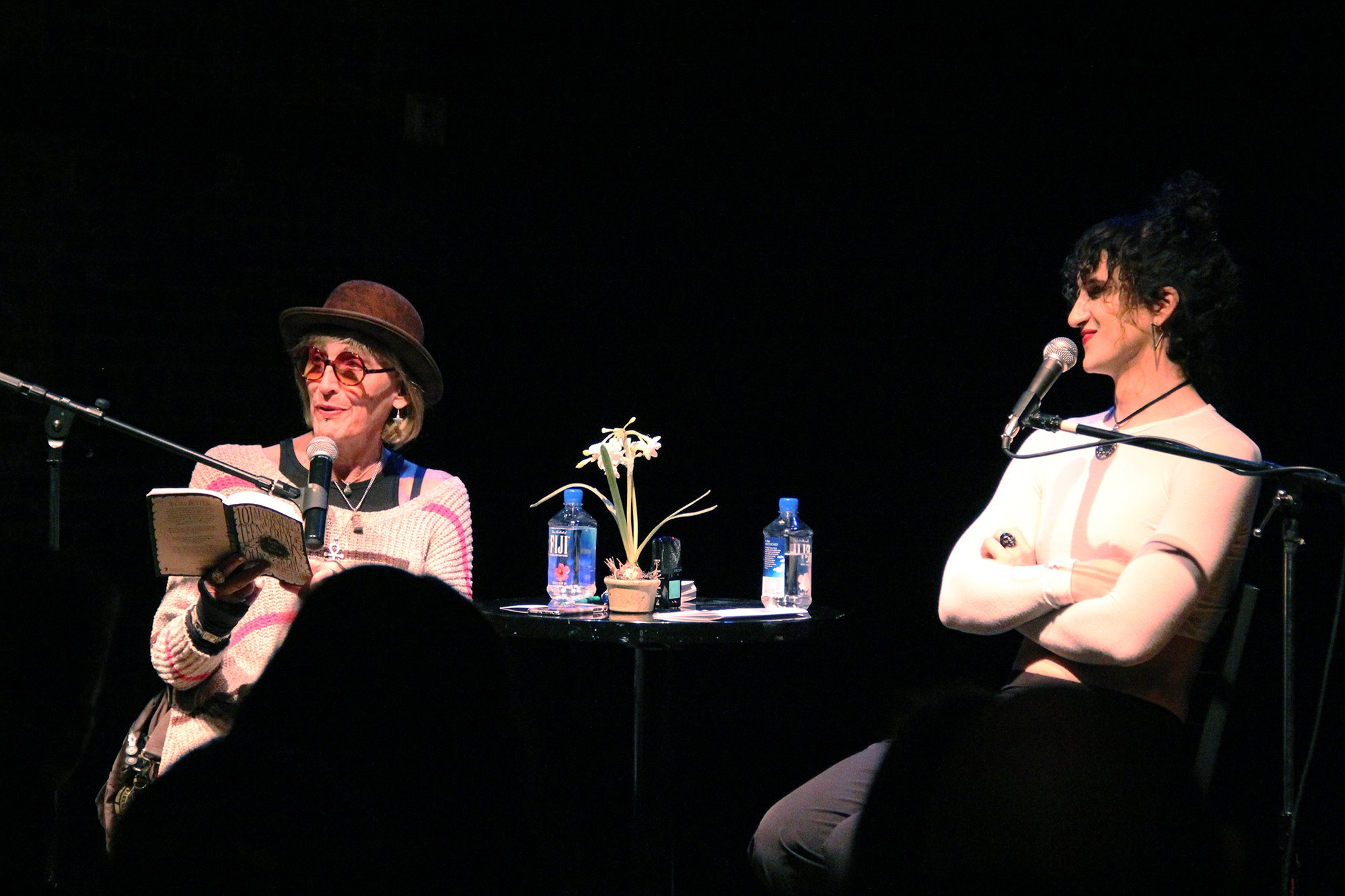 Kate Bornstein and Theda Hammel sit in chairs with microphones with a table between them with water for La MaMa's Squirts