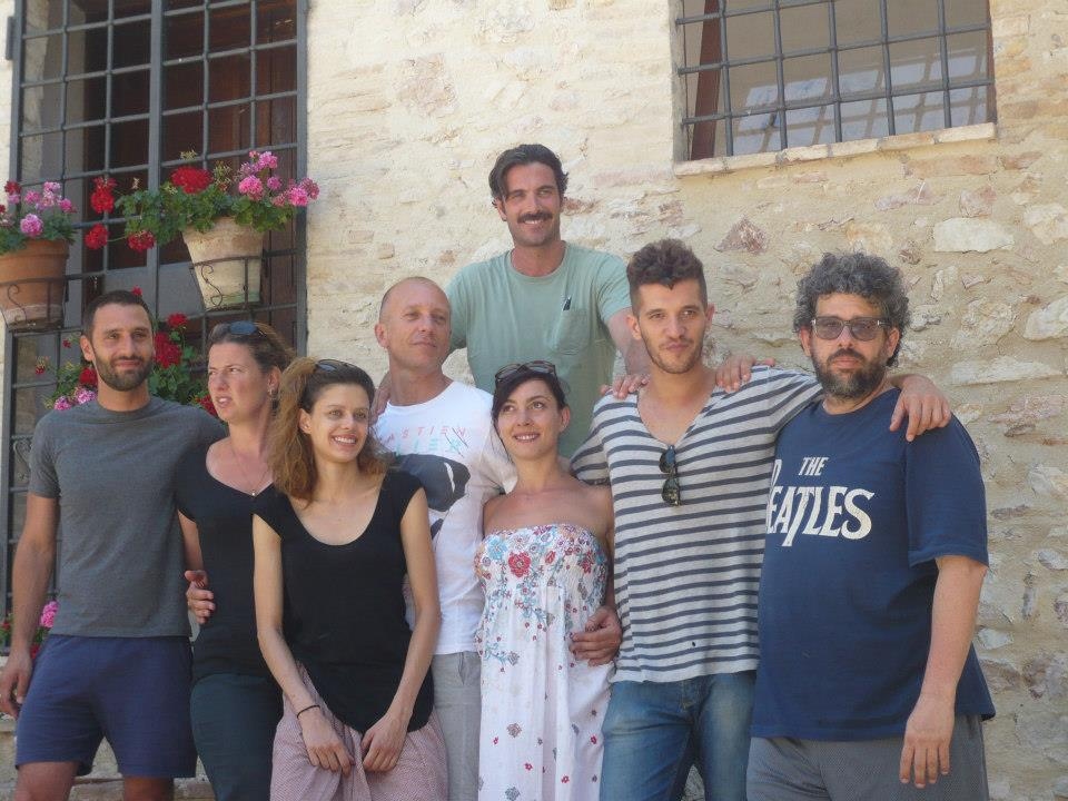 artists sit outside at La MaMa Umbria International posing outside with a stone wall behind them