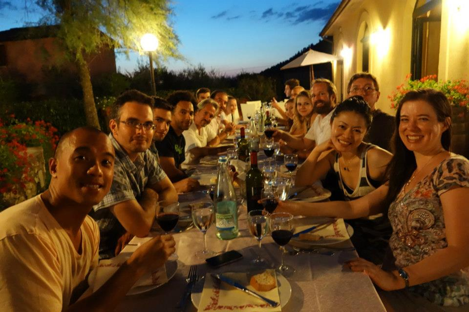 artists sit outside at La MaMa Umbria International eating at a long wooden dinner table outside by dim lights
