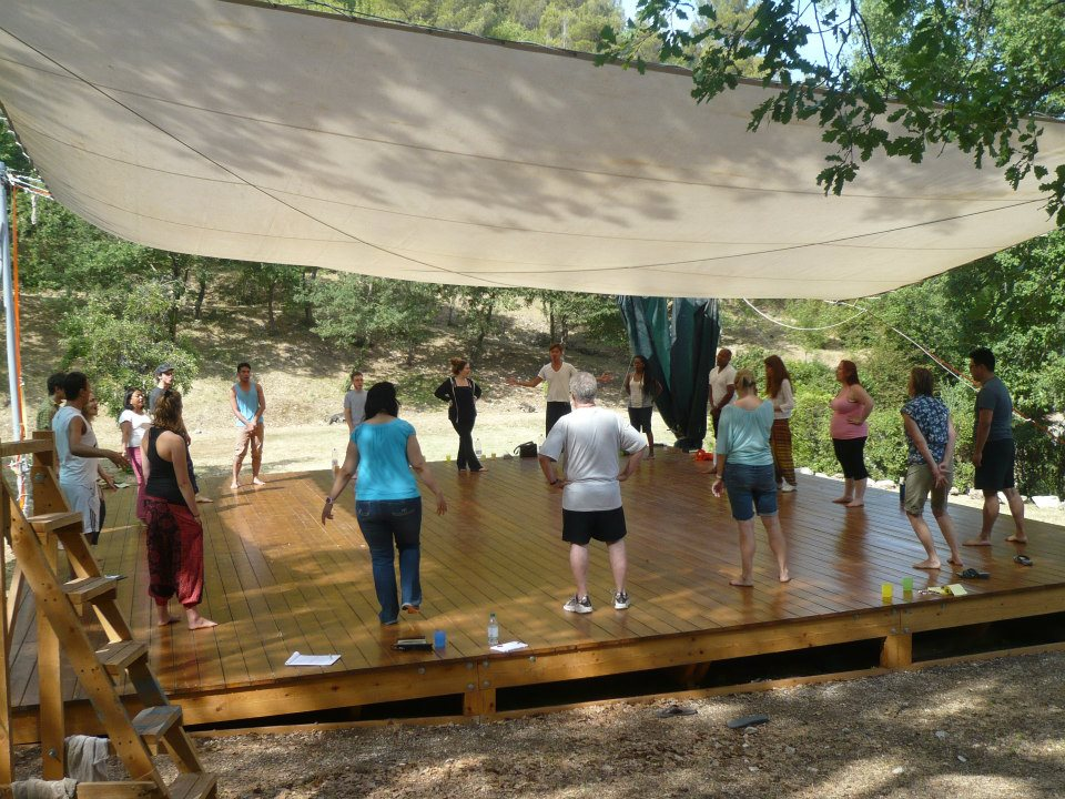 artists sit outside at La MaMa Umbria International working under a canopy outside on a wooden stage