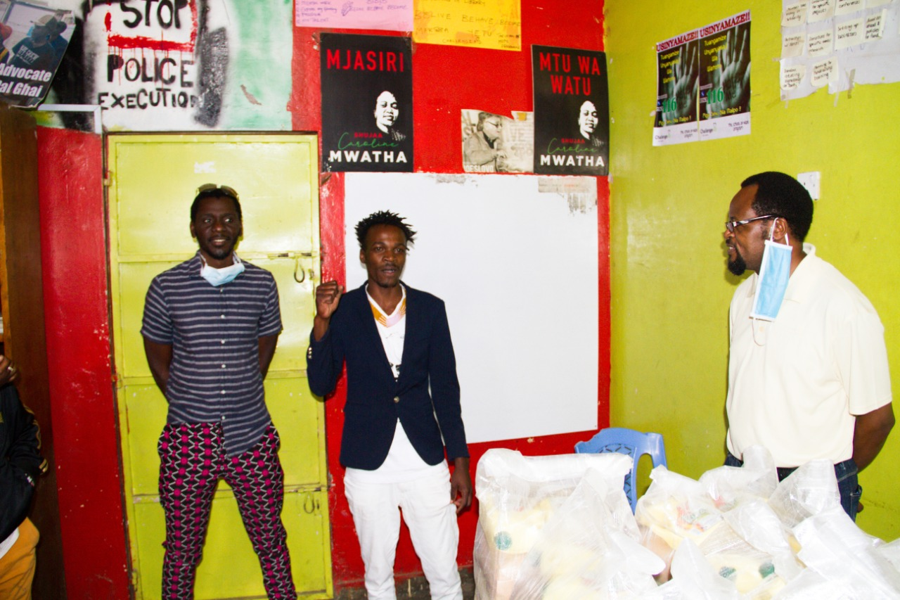 Members of Bold Theatre KE standing against a colorful wall