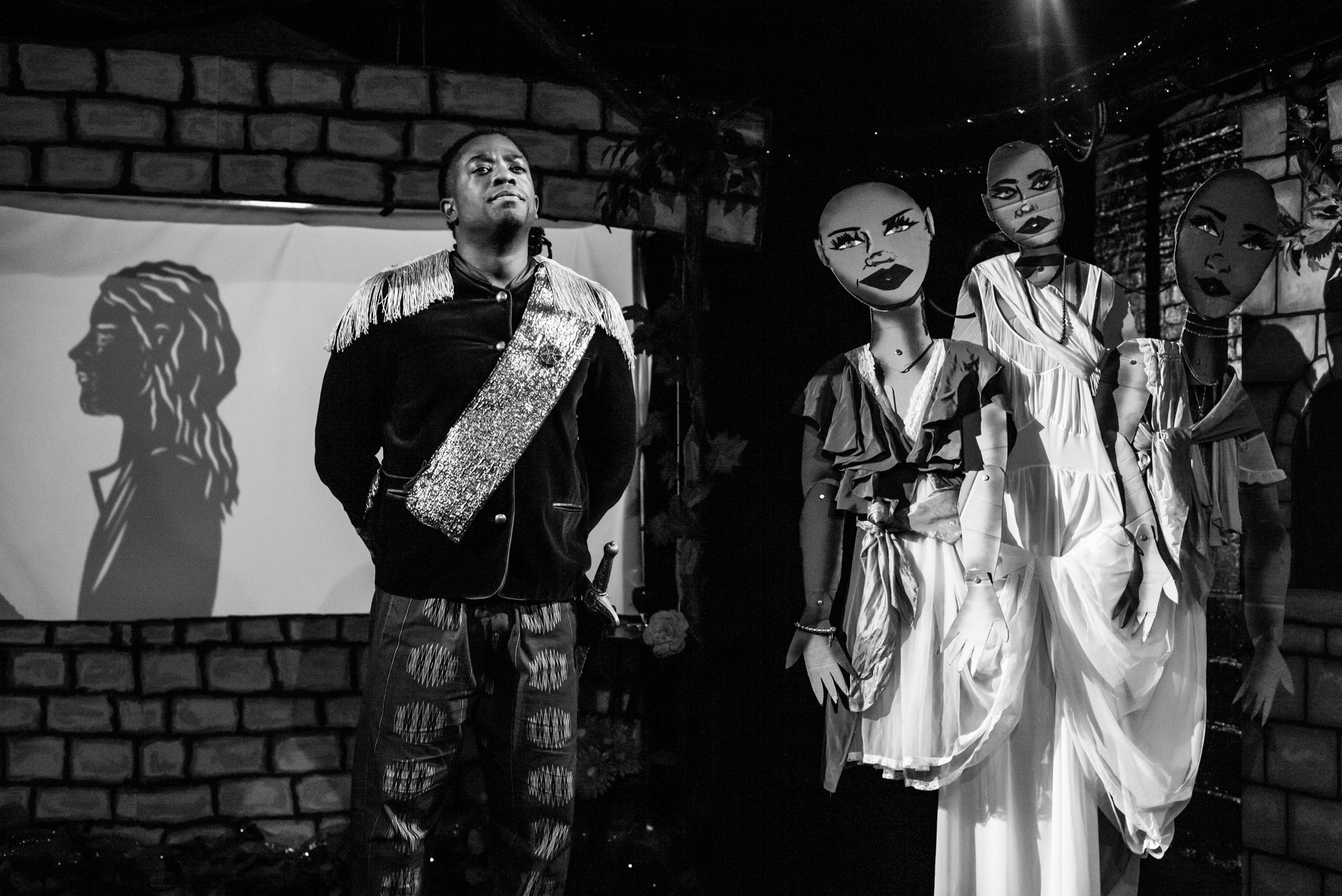 Midnight Radio Show performers on stage in black and white with puppets