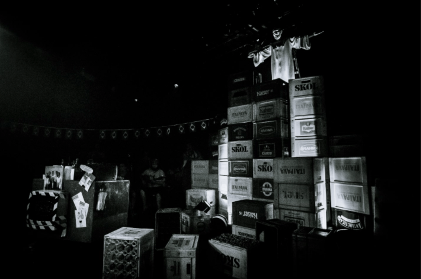 black and white photo of a person with open arms standing on top of a pile of crates