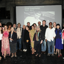group photo of people standing in front of a photo of sam shepard
