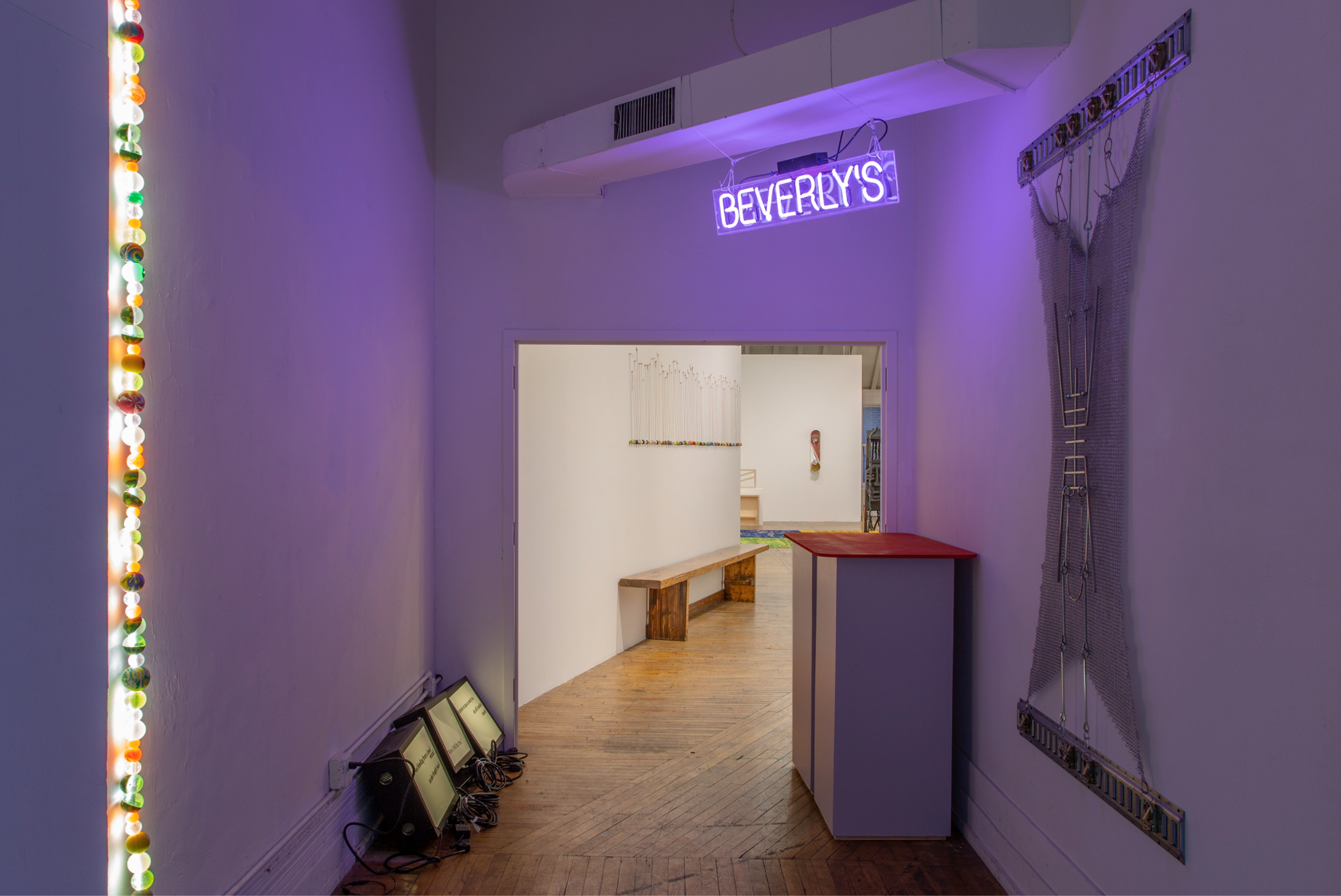 photo of the gallery space, neon sign above doorway that says Beverly's