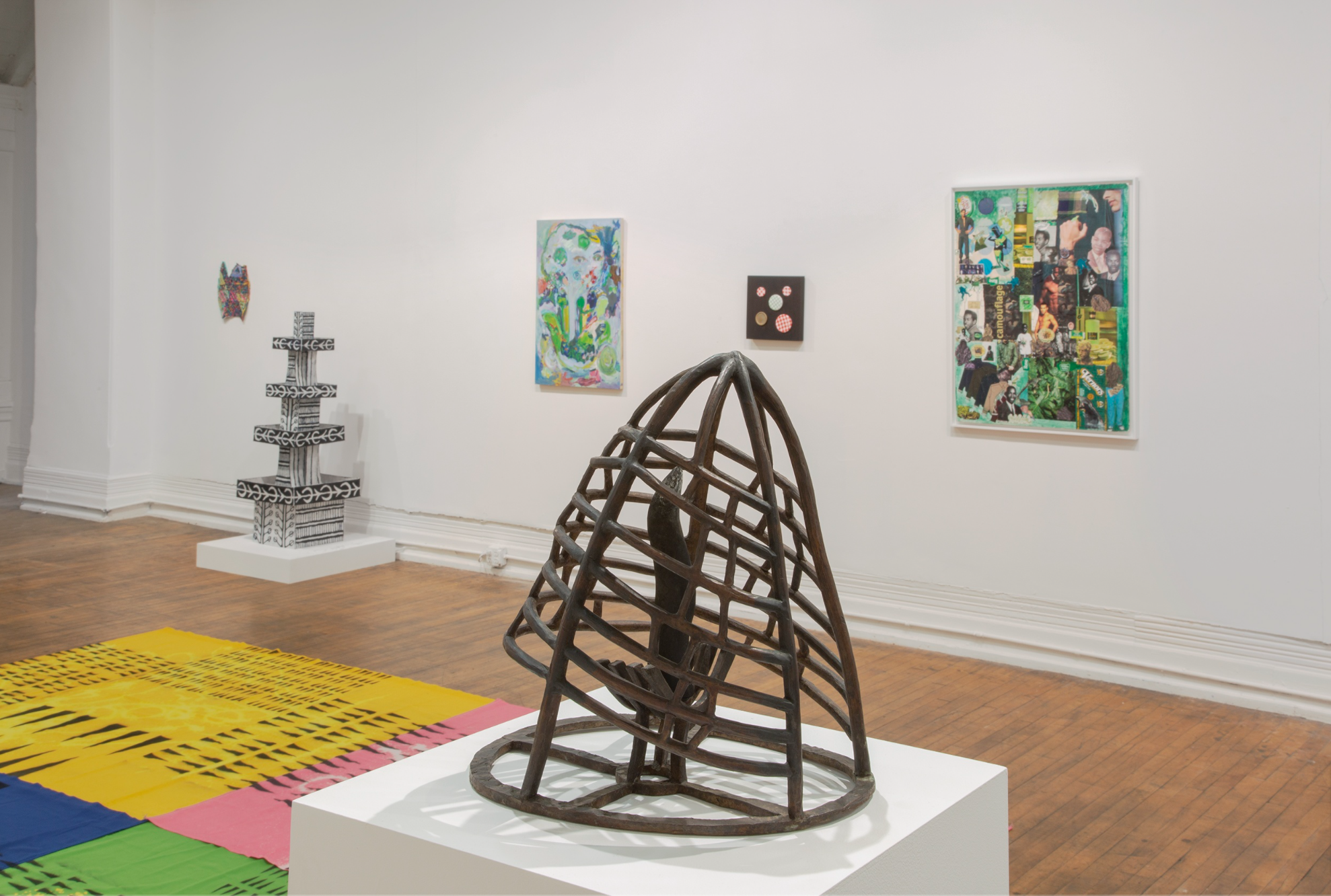 photo of the gallery space, in the foreground a cage sculpture