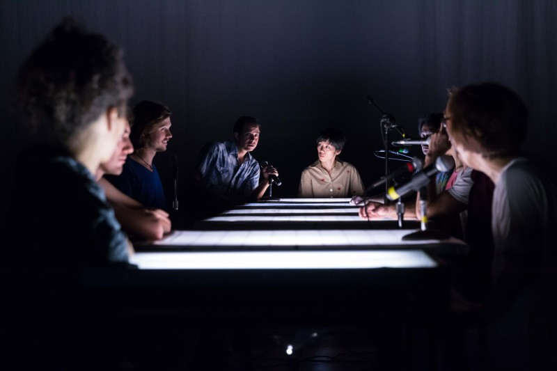 group of people sitting around a table. the people on the right are sitting in front of microphones