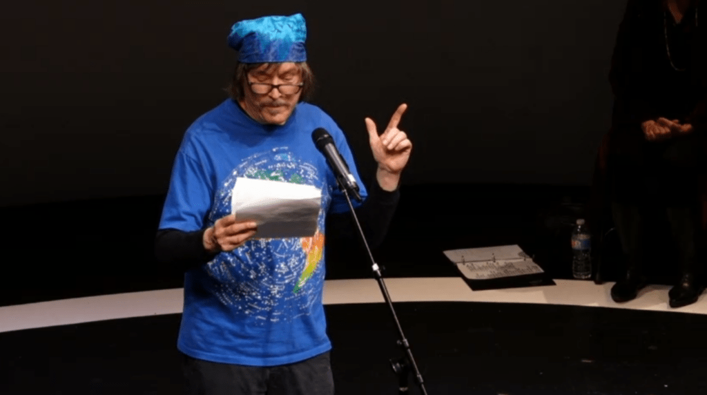 man onstage reading from a piece of paper into a microphone