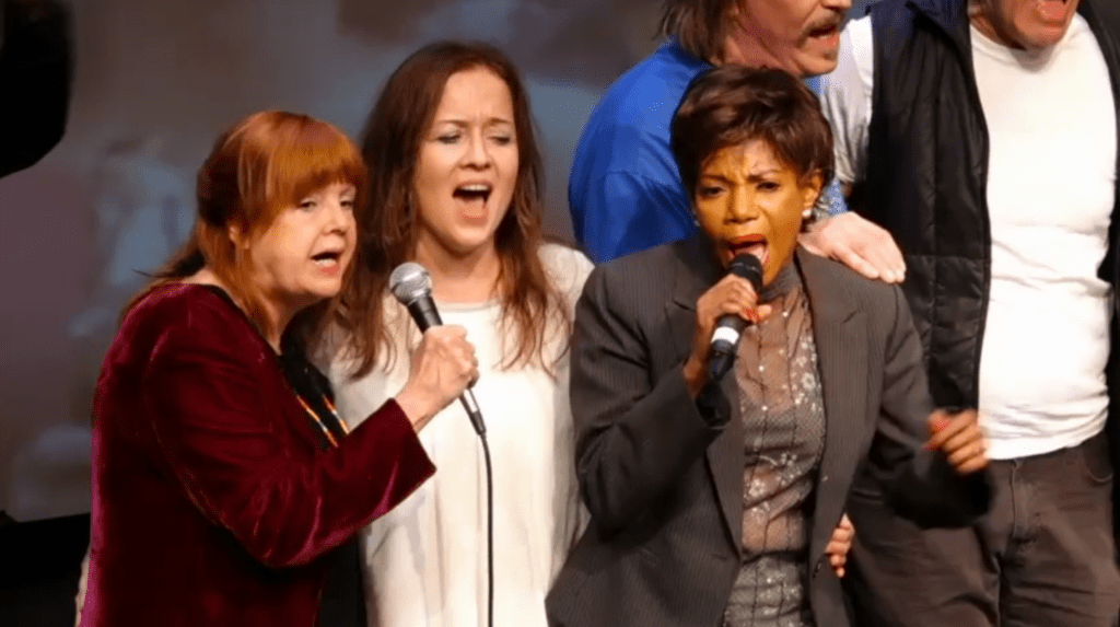three woman onstage singing. two women are holding microphones.