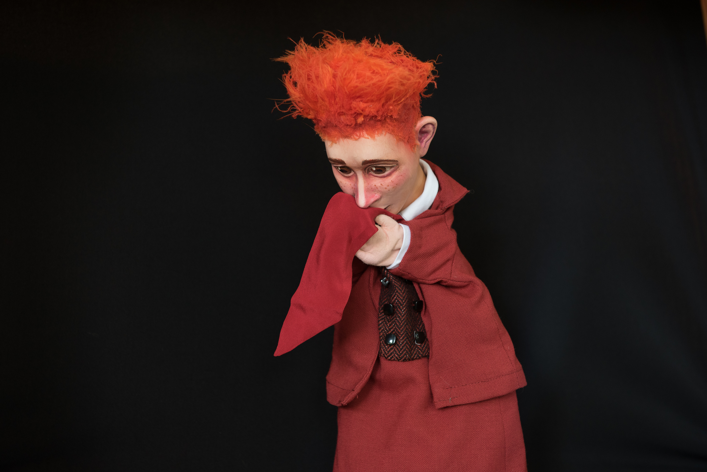 a red-haired puppet holding a red cloth