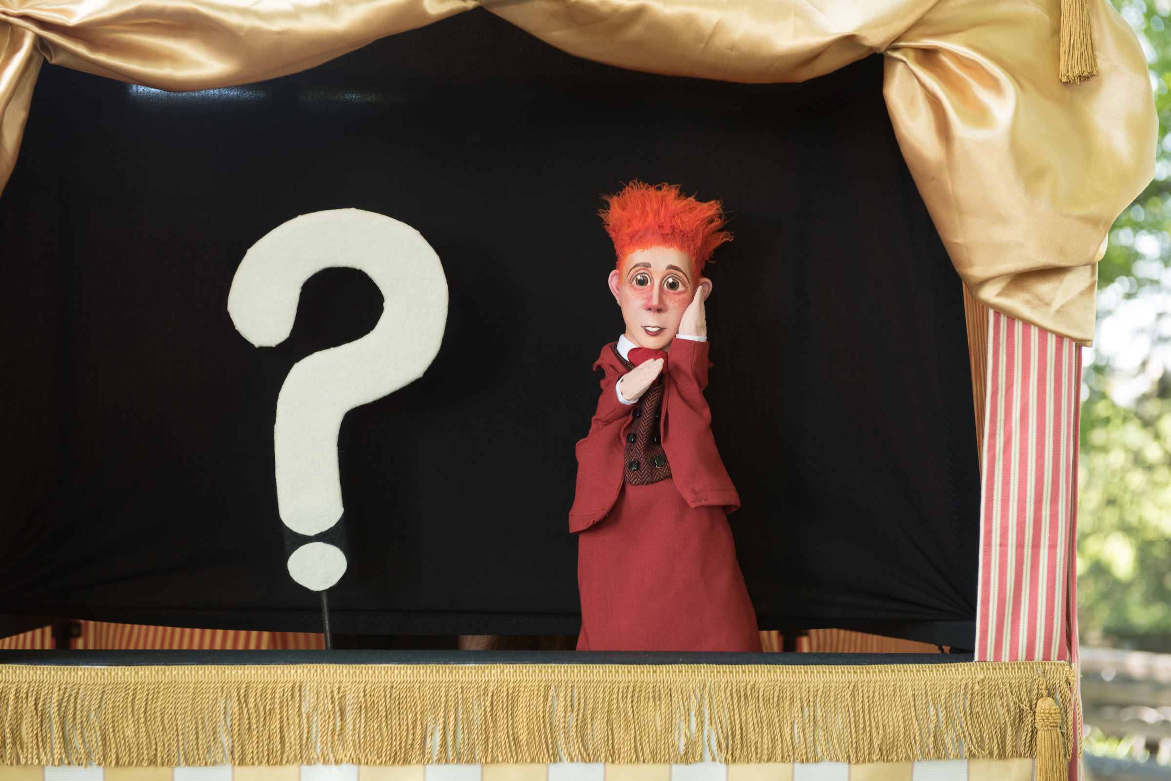 a red-haired puppet in front of a white question mark