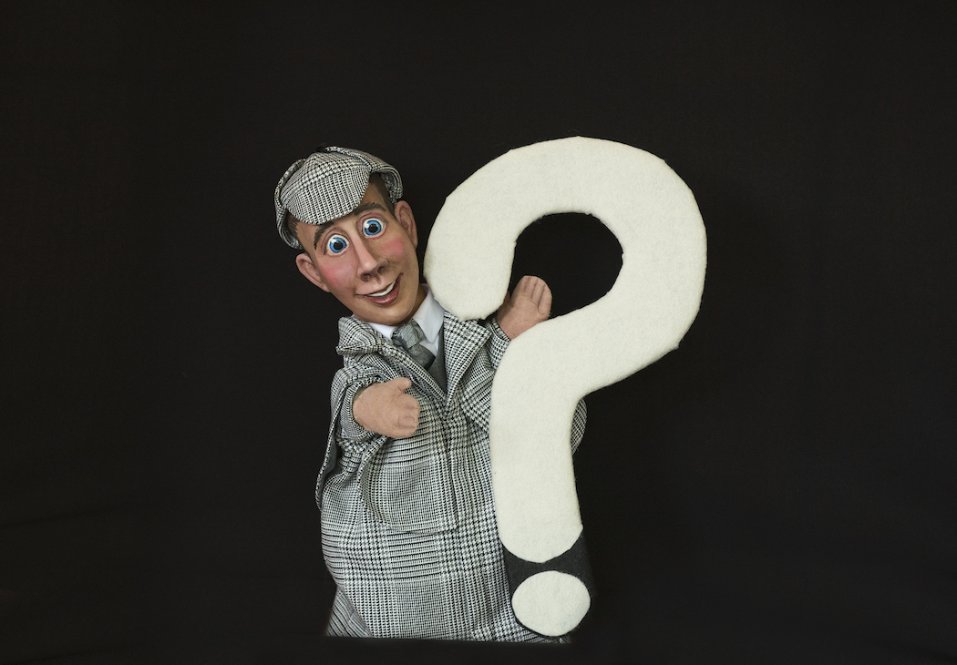 a puppet dressed as a detective holding a white question mark