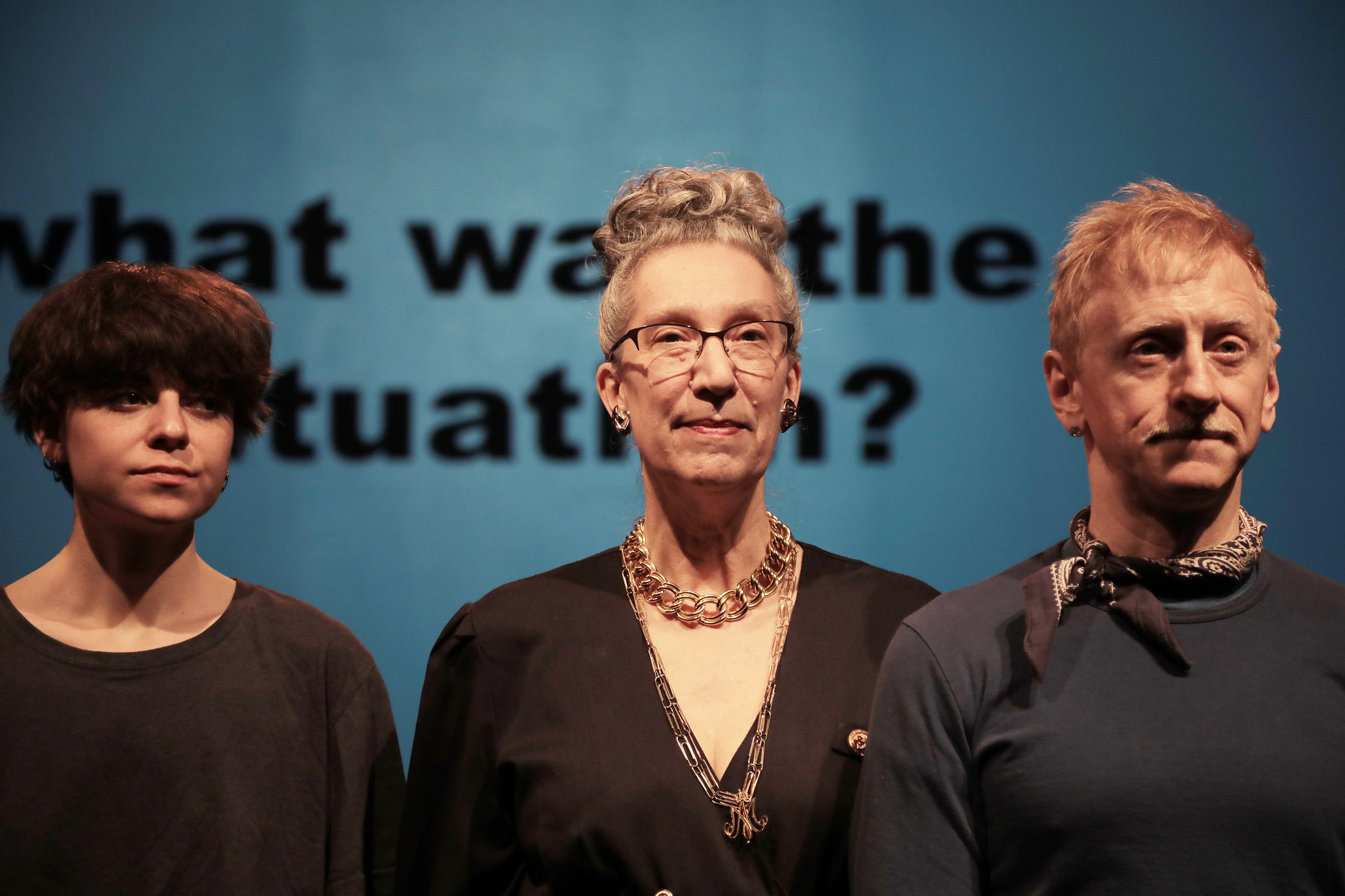 three people standing onstage